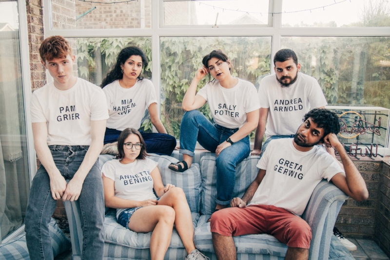 Girls on Tops, a group of young people sit round on a sofa in a conservatory wearing white tshirts with the names of female filmmakers on them in black capital letters